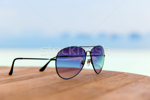 shades or sunglasses on table at beach Stock photo © dolgachov