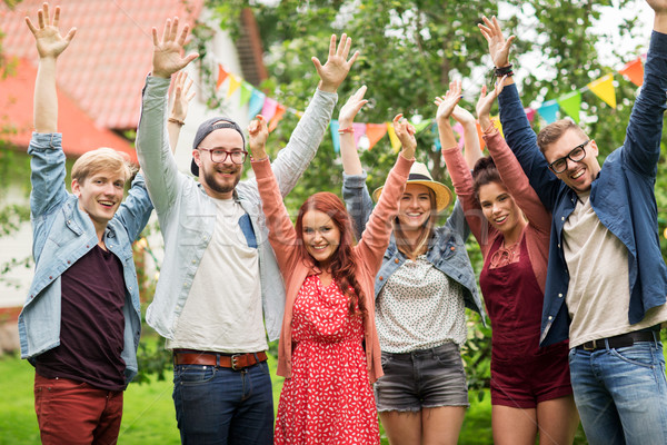happy teen friends waving hands at summer garden Stock photo © dolgachov