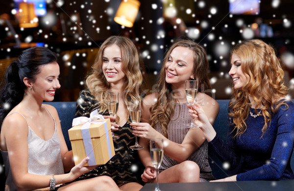 happy women with champagne and gift at night club Stock photo © dolgachov