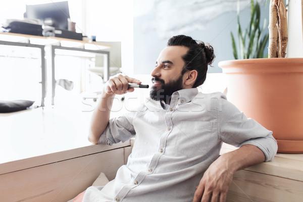 smiling man with beard and hair bun at office Stock photo © dolgachov