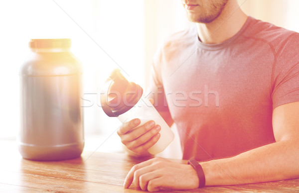 close up of man with protein shake bottle and jar Stock photo © dolgachov