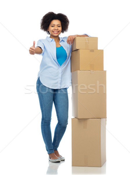 happy african woman with boxes showing thumbs up Stock photo © dolgachov
