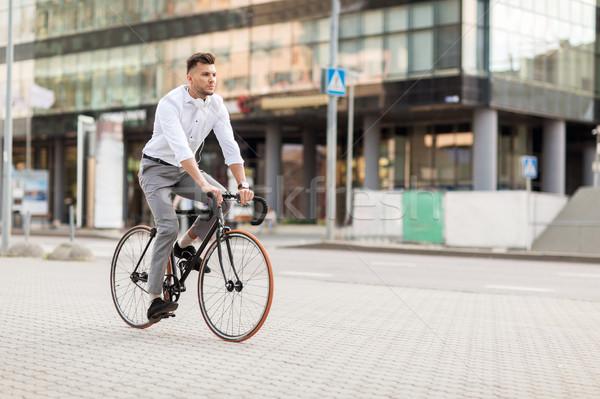 man with headphones riding bicycle on city street Stock photo © dolgachov
