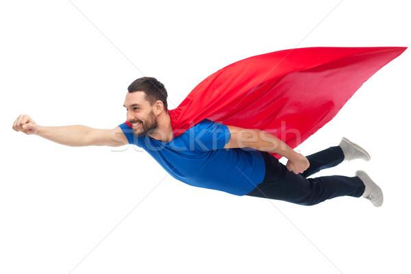 happy man in red superhero cape flying on air Stock photo © dolgachov