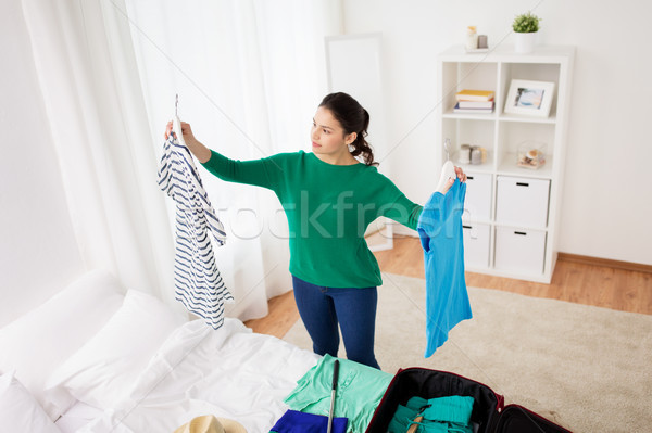 woman packing travel bag at home or hotel room Stock photo © dolgachov
