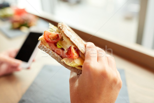 hand with salmon panini sandwich at restaurant Stock photo © dolgachov