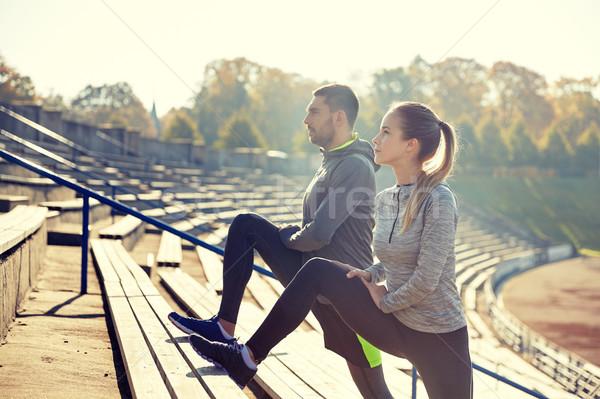 couple stretching leg on stands of stadium Stock photo © dolgachov