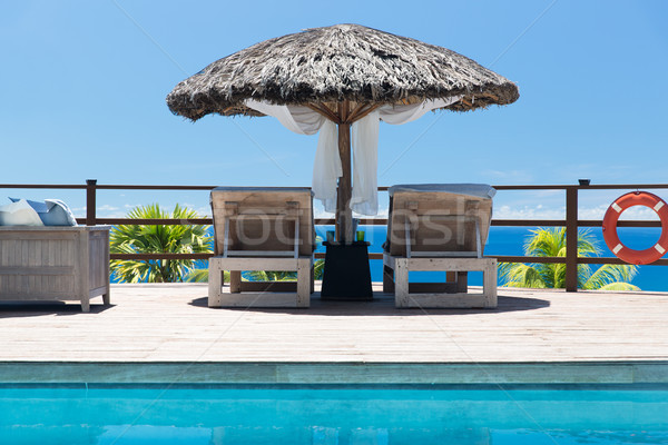 palapa and sunbeds at seaside swimming pool Stock photo © dolgachov