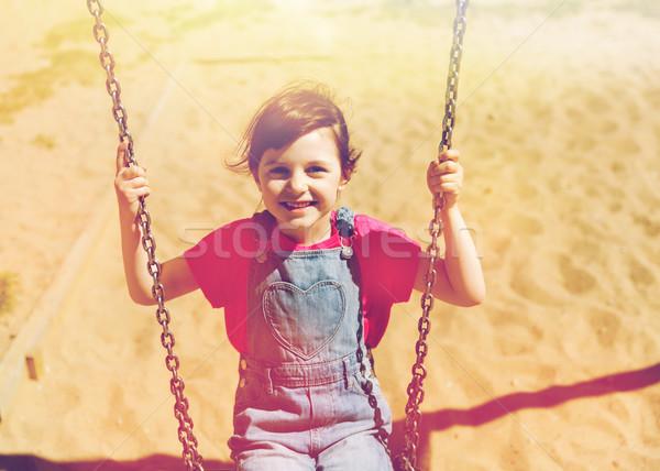 Felice bambina swing parco giochi estate infanzia Foto d'archivio © dolgachov