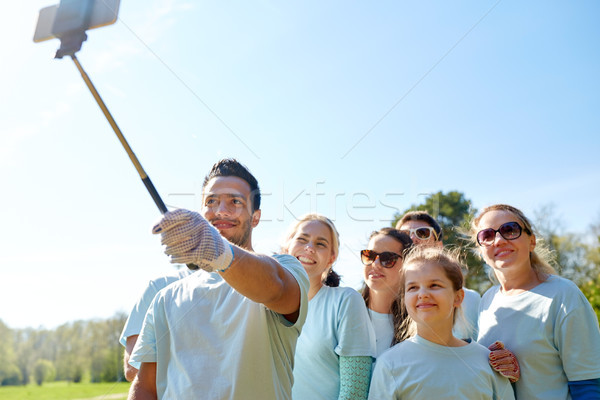 group of volunteers taking smartphone selfie Stock photo © dolgachov