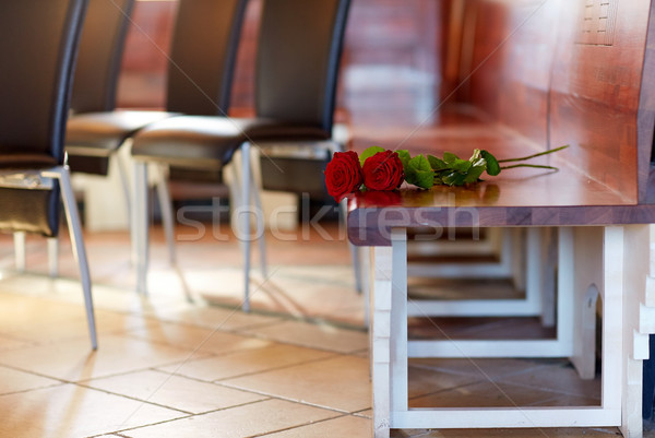 red roses on bench at funeral in church Stock photo © dolgachov