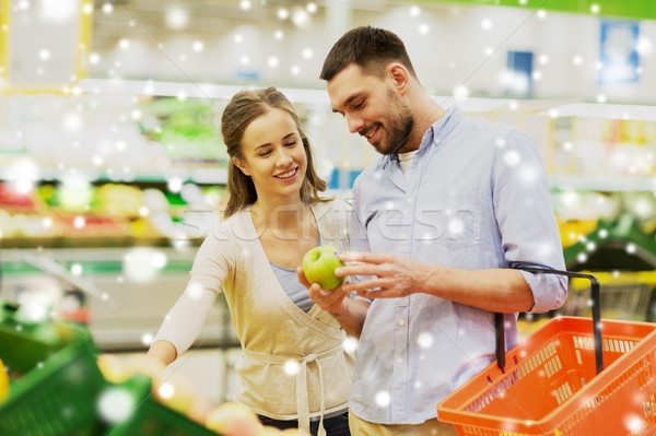happy couple buying apples at grocery store Stock photo © dolgachov