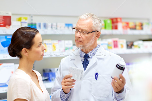 apothecary and woman with drug at pharmacy Stock photo © dolgachov