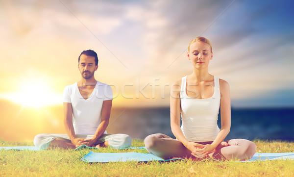 happy couple making yoga and meditating outdoors Stock photo © dolgachov