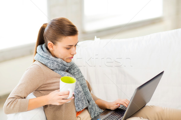 diseased woman in scarf using laptop at home Stock photo © dolgachov