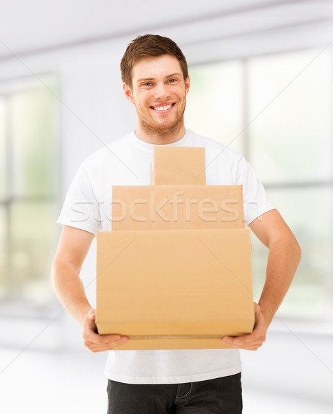 smiling man carrying carton boxes at home Stock photo © dolgachov