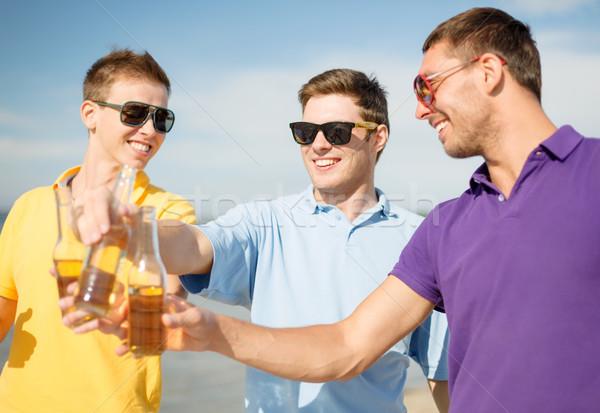 group of male friends having fun on the beach Stock photo © dolgachov