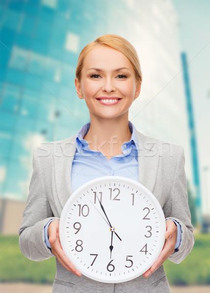 smiling businesswoman with wall clock Stock photo © dolgachov