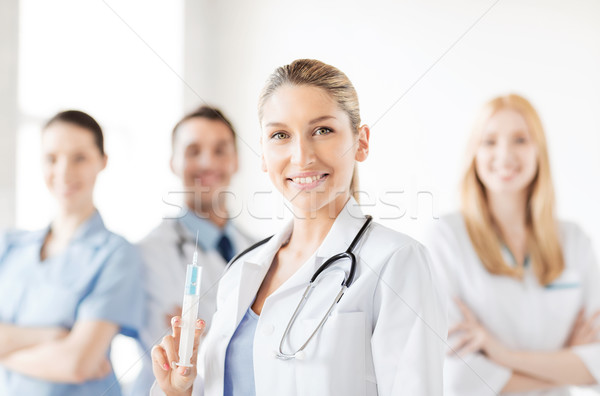 female doctor holding syringe with injection Stock photo © dolgachov