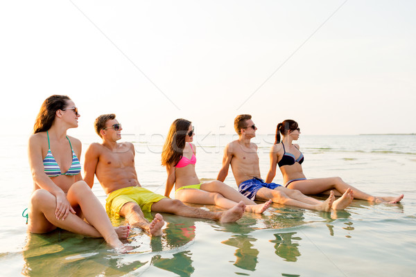 smiling friends in sunglasses on summer beach Stock photo © dolgachov