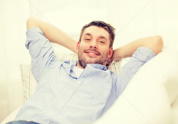 smiling man lying on sofa at home Stock photo © dolgachov