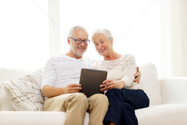 happy senior couple with tablet pc at home Stock photo © dolgachov