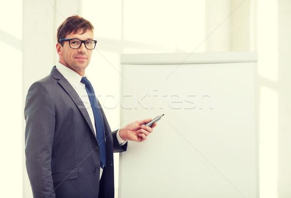 businessman pointing to flip board in office Stock photo © dolgachov