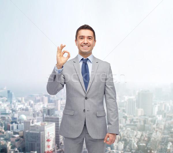 Feliz empresário terno sinal da mão Foto stock © dolgachov