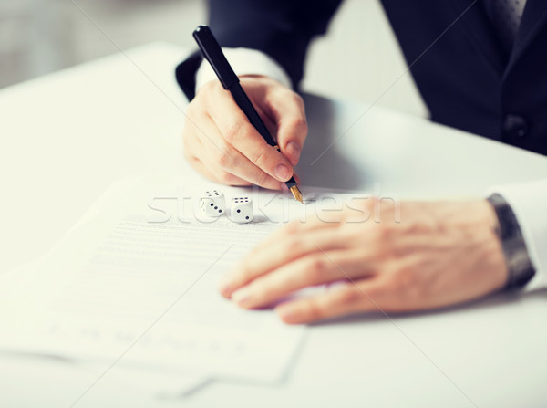 man hands with gambling dices signing contract Stock photo © dolgachov