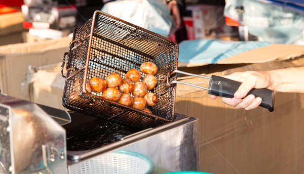 close up of cook frying meatballs at street market Stock photo © dolgachov