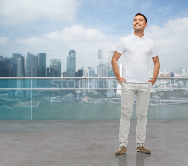 smiling man with hands in pockets looking up Stock photo © dolgachov