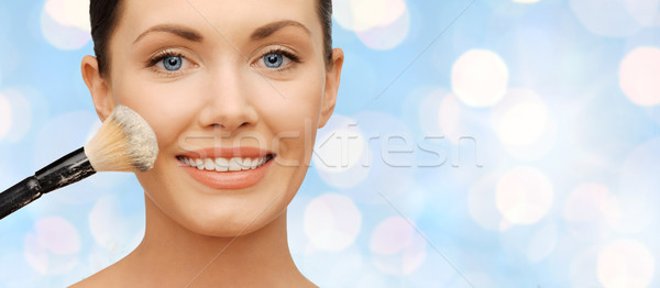 happy woman applying powder foundation with brush Stock photo © dolgachov
