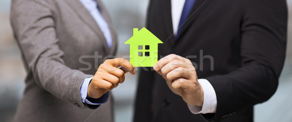 businessman and businesswoman holding green house Stock photo © dolgachov