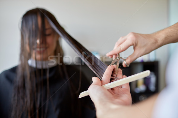 happy woman with stylist cutting hair at salon Stock photo © dolgachov