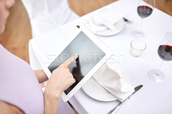 close up of woman with tablet pc at restaurant Stock photo © dolgachov