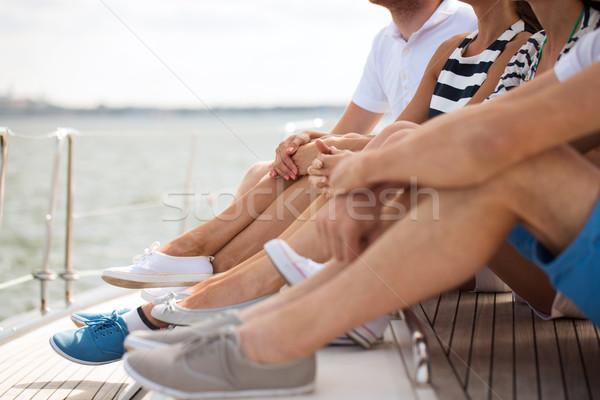 Amici gambe seduta yacht deck Foto d'archivio © dolgachov