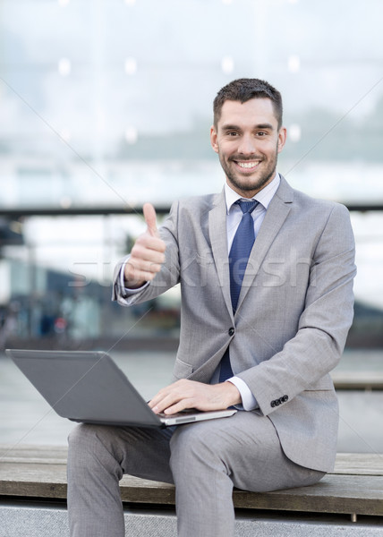smiling businessman working with laptop outdoors Stock photo © dolgachov