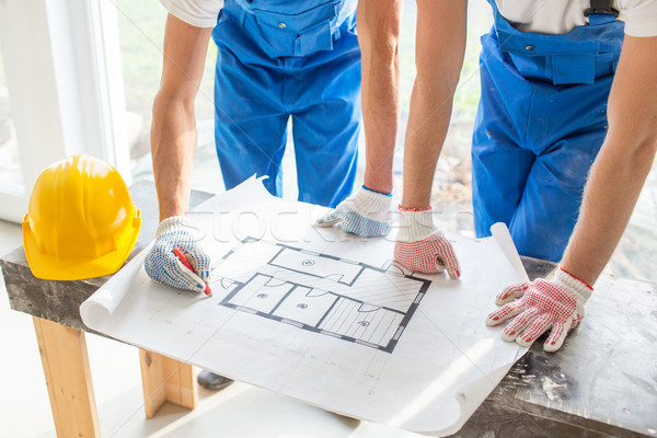 close up of builders discussing blueprint Stock photo © dolgachov
