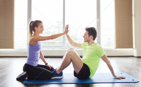 man with personal trainer doing sit ups in gym Stock photo © dolgachov