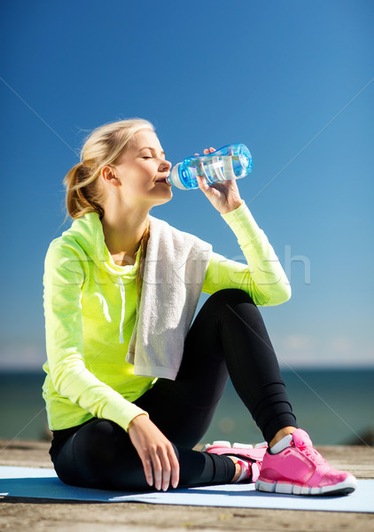 Stock photo: woman drinking water after doing sports outdoors
