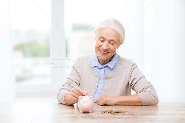 senior woman putting money to piggy bank at home Stock photo © dolgachov