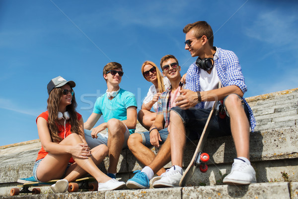 happy teenage friends with longboard on street Stock photo © dolgachov