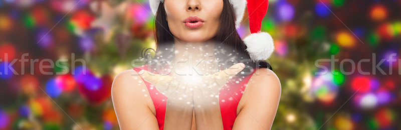 close up of woman in santa hat blowing on palms Stock photo © dolgachov