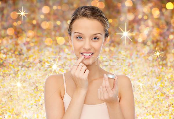 Sorridente mulher jovem lábio bálsamo lábios Foto stock © dolgachov