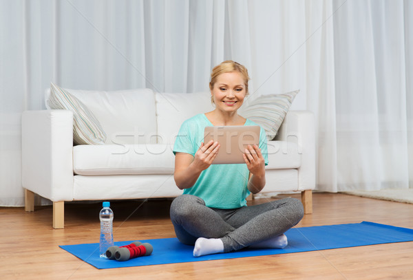 smiling woman with tablet pc exercising at home Stock photo © dolgachov