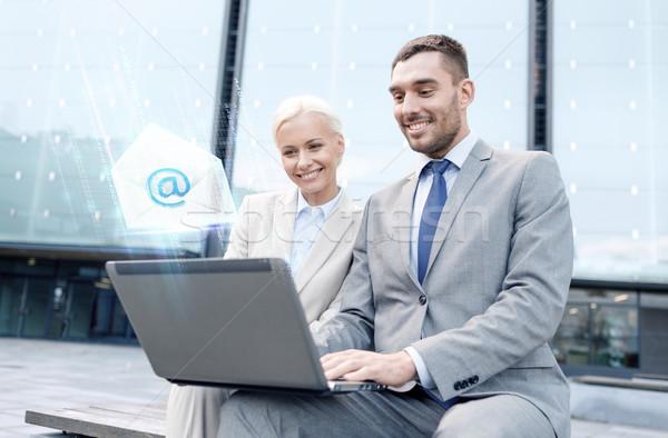 Mosolyog üzletemberek laptop küldés email üzlet Stock fotó © dolgachov