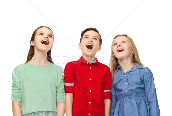 amazed boy and girls looking up Stock photo © dolgachov