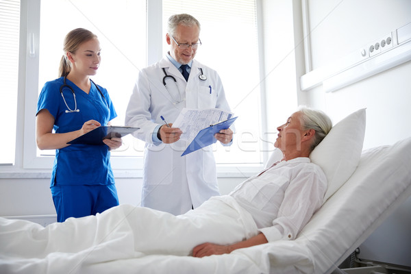 doctor and nurse visiting senior woman at hospital Stock photo © dolgachov
