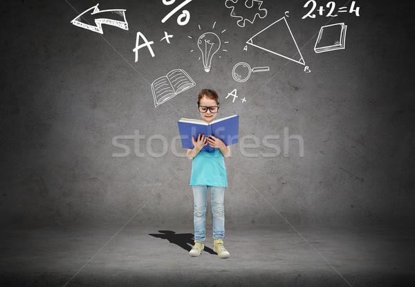 little girl in eyeglasses reading math textbook Stock photo © dolgachov