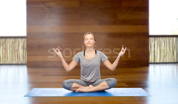 Stock photo: woman making yoga meditation in lotus pose on mat